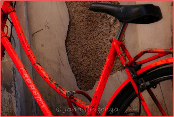 Red Bike Against Wall in Sicily, copyright Jann Huizenga