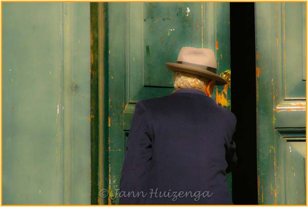 Man Pushing Open Green Door, copyright Jann Huizenga