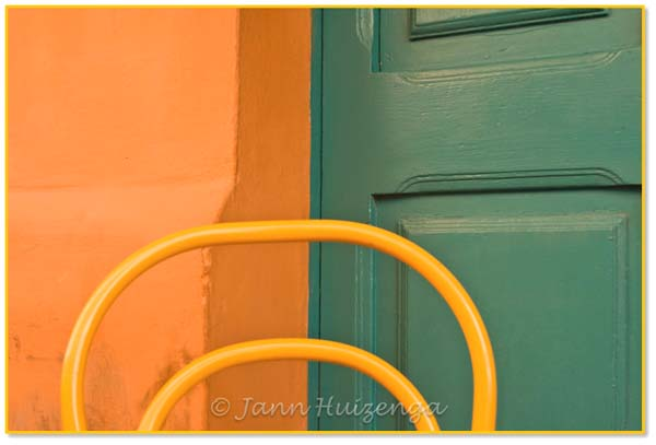 Chair against green door in Italy, copyright Jann Huizenga