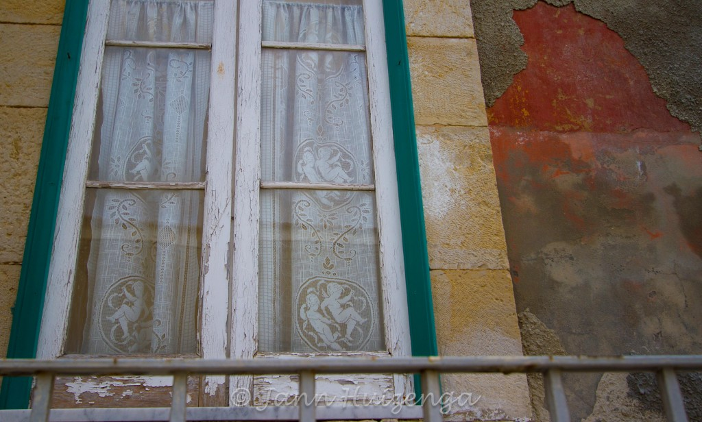 Lace with Cherubs in Window in Southeast Sicily, copyright Jann Huizenga