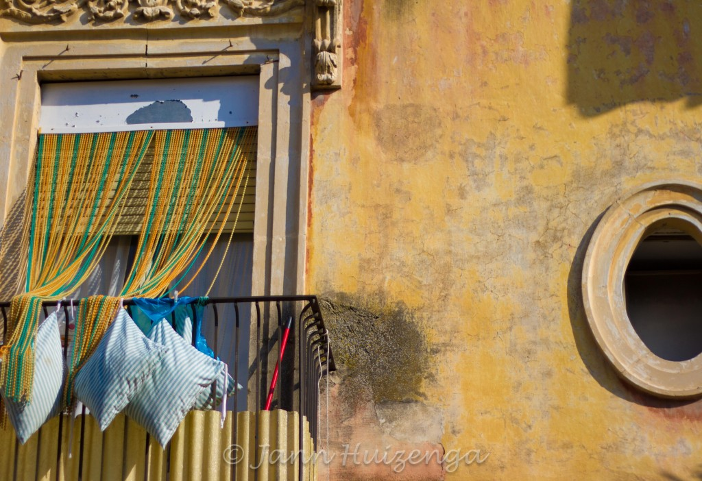 Window with Pillows Hanging Outside in Southeast Sicily, copyright Jann Huizenga
