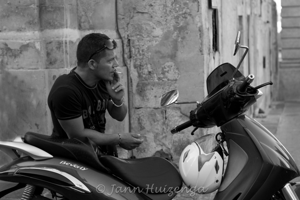 Sicilian Man in Noto Leaning on Motorcycle, copyright Jann Huizenga