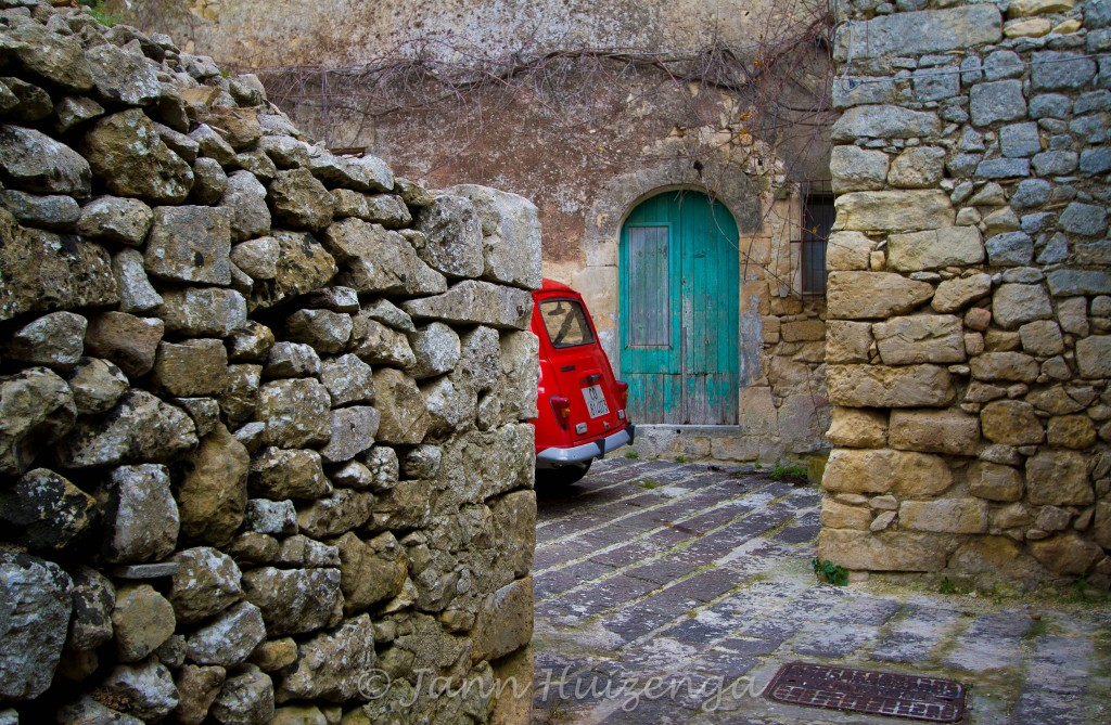 Red Car in Stone Courtyard in Sicily, copyright Jann Huizenga
