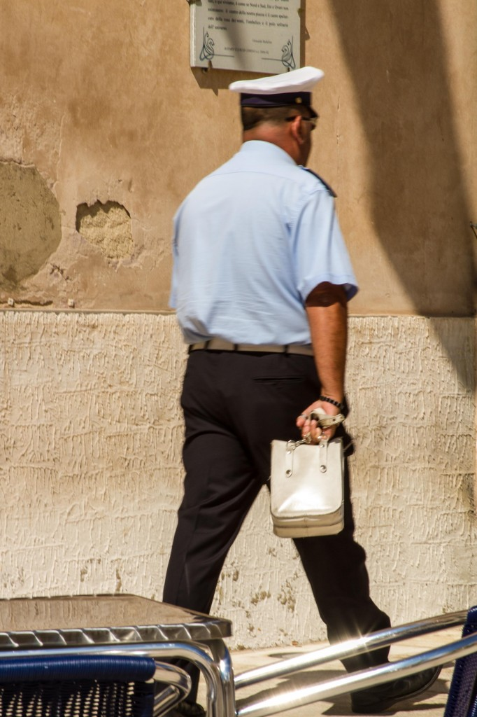 Policeman with Man Bag in Sicily, copyright Jann Huizenga