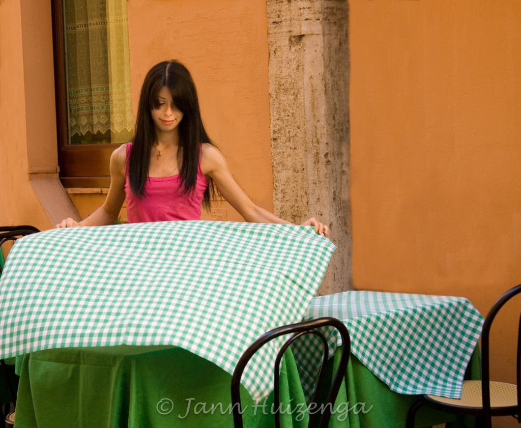 Waitress in Rome with checked tablecloth; copyright Jann Huizenga