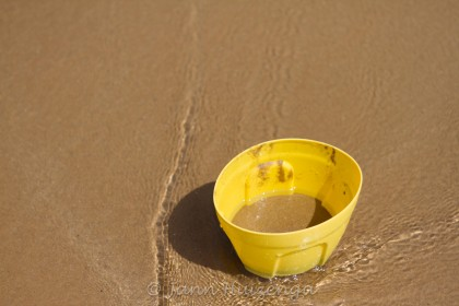 Yellow Bucket on Beach, copyright Jann Huizenga