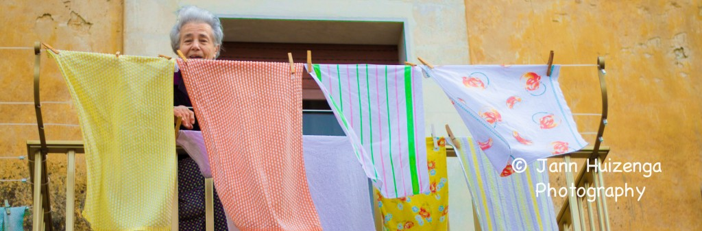 Sicilian woman hanging laundry on balcony, copyright Jann Huizenga